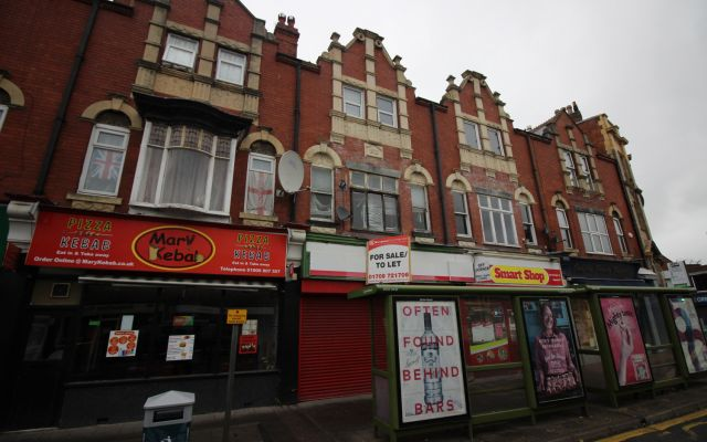 Three-storey commercial building comprising ground floor retail unit with upper floor living accommodation.